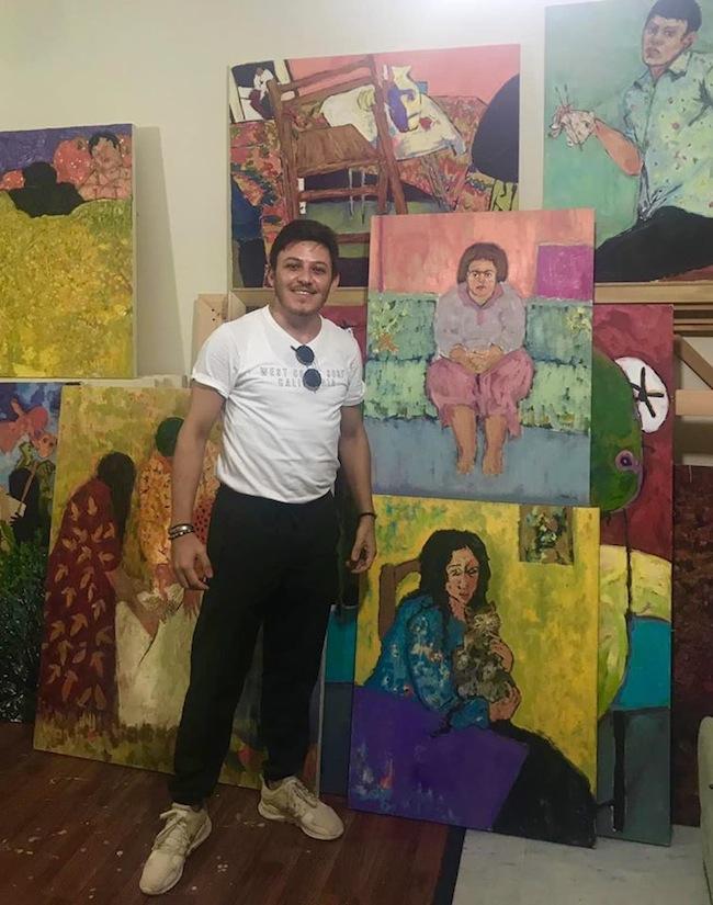 Anas Albraehe davanti ai suoi dipinti. Courtesy of Anas Albraehe